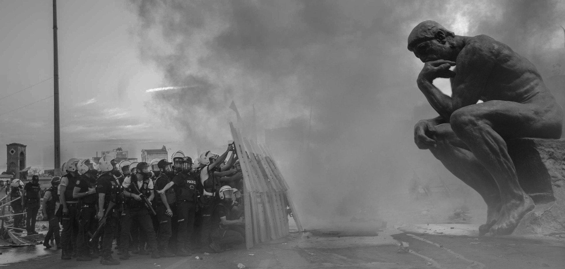 Una gruppo di poliziotti si ripara formando un muro con gli scudi della polizia. Al di là di questo muro, la statua del pensatore di Rodin.