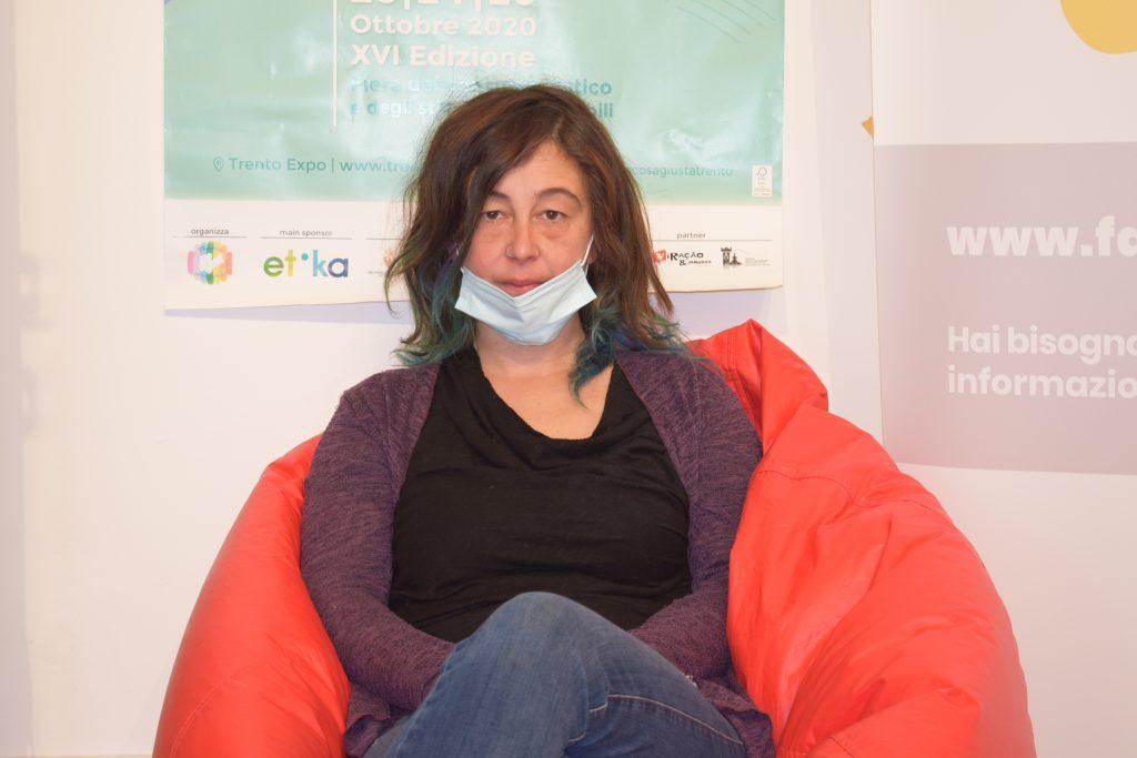 Roberta è seduta su una poltrona rossa mentre viene intervistata. Sullo sfondo la locandina di Fa' la cosa giusta! Trento